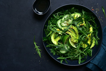 Green vegetable salad with arugula, cucumber and avocado. Top view with copy space.