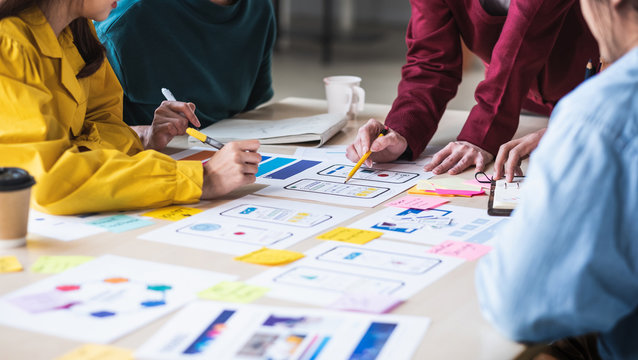 Close up ux developer and ui designer brainstorming about mobile app interface wireframe design on table with customer breif and color code at modern office.Creative digital development agency.