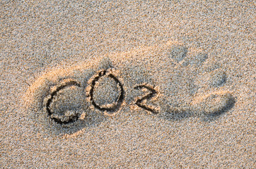 Eco-friendly carbon footprint message with handwritten CO2 text in the outline of a foot on a grainy golden sand beach
