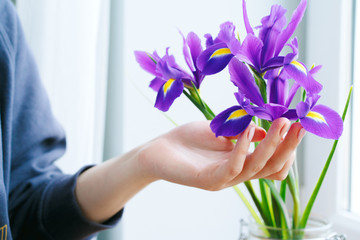 Deurstickers Iris Woman hand touching irises in a vase on windowsill
