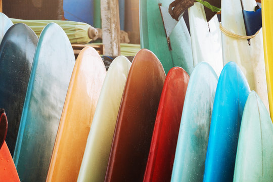 Close up Set of colorful surfboard for rent on the beach. Multicolored surf boards different sizes and colors surfing boards on stand, surfboards rental place