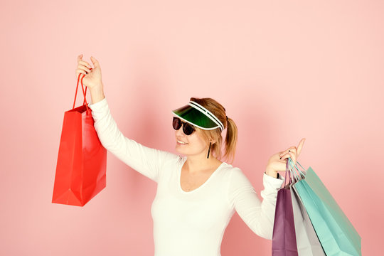 smiling young woman with sunglasses and retro sun visor carrying colored shopping bags with raised arms on pink background