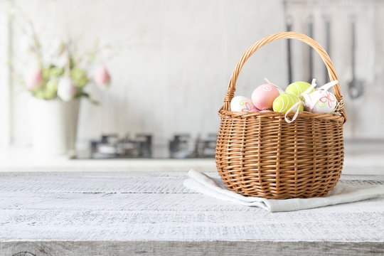 Wicker basket with easter colorful eggs on kitchen wooden table. Spring easter composition. Space for text.