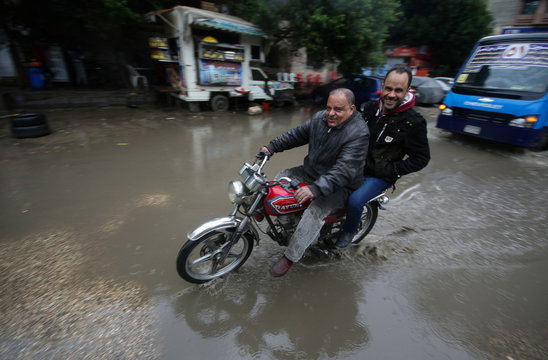 People ride a motorcycle during a thunderstorm and heavy rains in downtown of Cairo