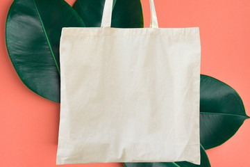 Blank cotton white shopper tote bag on pink background with green leaves. Mock up template for...