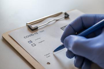 Arzt füllt positiven COVID-19 Test eines Patienten aus