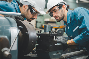 Two maintenance engineers discuss inspect relay checking machinery and repair system in a factory. They work a heavy industry manufacturing factory. Fotomurales