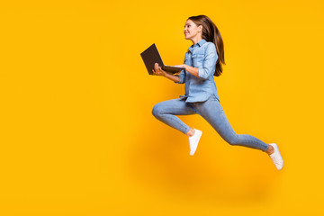 Full body profile photo of pretty business lady jump high holding notebook hands hurry work browsing laptop wear casual denim outfit white sneakers isolated yellow color background Wall mural
