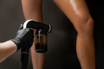 Woman body paint instant tan spray skintone with airbrush in professional beauty salon on black background