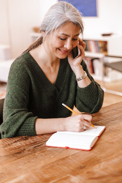 Photo of smiling woman talking on cellphone and making notes in diary