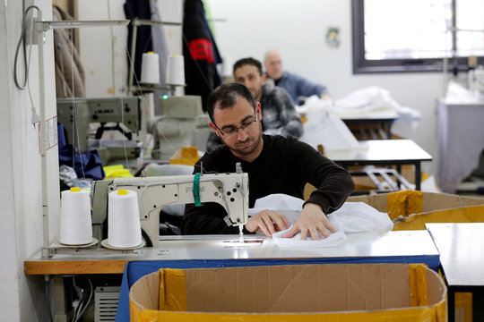 A Palestinian man sews a protective medical suit amid precautions against coronavirus, in Hebron in the Israeli-occupied West Bank