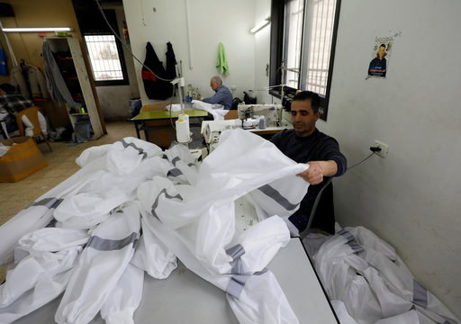 A Palestinian man assembles protective medical suits in a sewing factory amid precautions against coronavirus, in Hebron in the Israeli-occupied West Bank