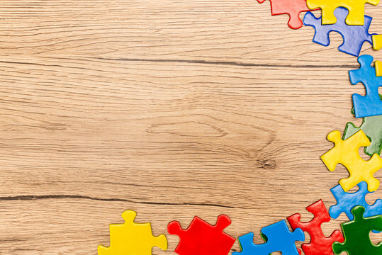 Top view of multicolored pieces of puzzle on wooden background, autism concept