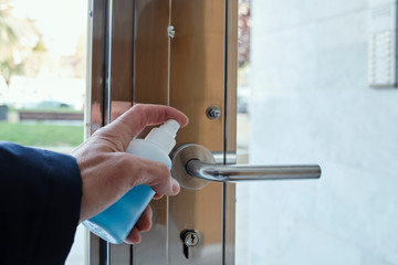 man disinfecting the handle of the front door