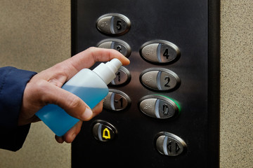 Door stickers Asia Country man disinfecting the buttons of an elevator