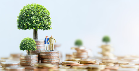 Miniature people: Elderly people sitting on coins stack. social security income and pensions. Money saving and Investment. Time counting down for retirement concept.