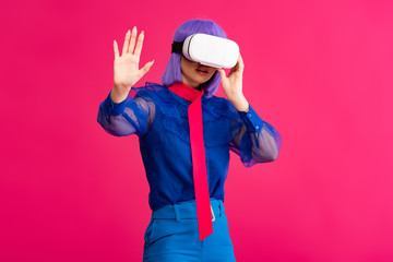fashionable pop art girl in blue blouse using vr headset, isolated on pink