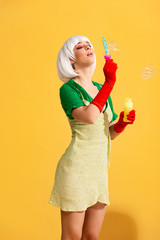 beautiful pop art girl in white wig blowing soap bubbles, on yellow