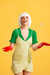 attractive happy pop art girl in white wig with soap bubbles, on yellow