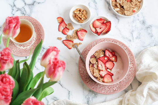 Breakfast scene with yogurt, granola and dried strawberries bowl and a cup of tea on a mable table
