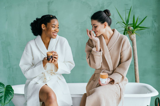 Cheerful pretty multiracial young ladies friends wear silk robes having fun hold glasses with champagne sit on bed in hotel, happy diverse girls bride and bridesmaid celebrate bachelorette spa party