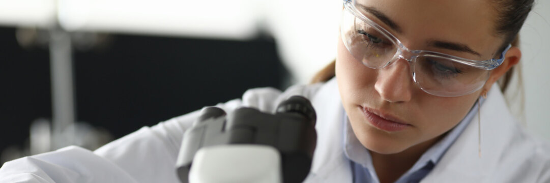 Portrait of concentrated serious woman putting material under microscope. Working process at laboratory office. Medicine investigation and analysis concept