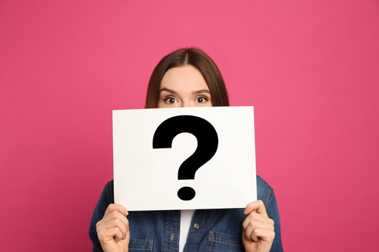 Emotional woman holding question mark sign on pink background