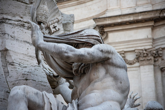 Fountain of the Four Rivers by Gian Lorenzo Bernini, baroque creation located in the center of Piazza Navona, Rome, Italy. Giant white marble statue represents the Nile river allegory.
