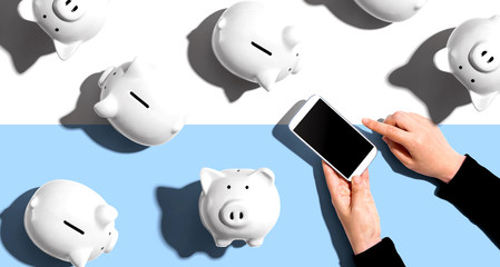 Piggy banks with person using a smartphone - flat lay