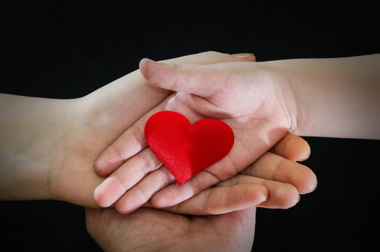 adult and child hands holding red heart, health care, donate and family insurance concept,world heart day, world health day, CSR concept, adoption foster family.Image is tinted