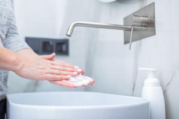 Woman washing hands with foam soap. Hygiene, preventing coronavirus
