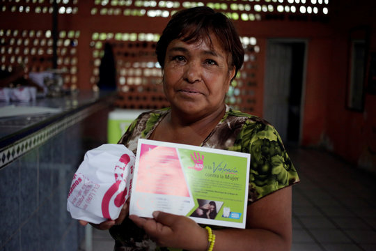 A woman poses for a pictured holding a package of tortillas wrapped in paper with contact information to help women victims of gender violence, as a part of a government program called Break the Silence, at a tortilla stall in Nuevo Laredo
