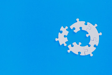 White unfinished jigsaw puzzle pieces on a blue background