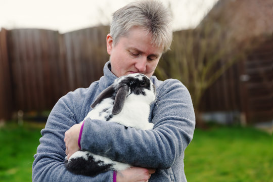 woman holds a pet rabbit in the arms