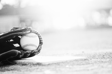 baseball and glove on ball field in black and white with copy space for sports seasno.
