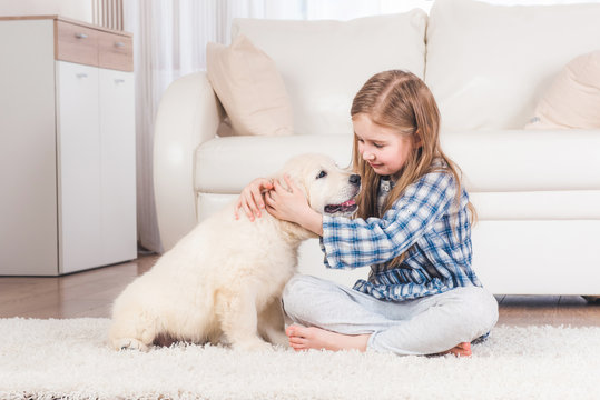 Smiling little girl sitting with fluffy retriever puppy at home