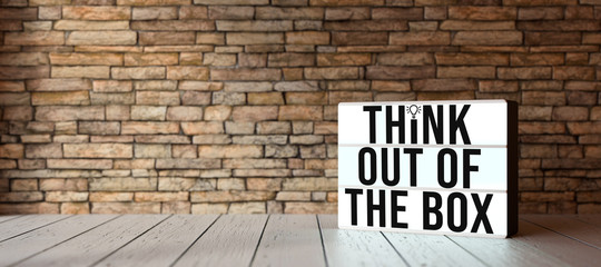 lightbox with message THINK OUTSIDE THE BOX in front of brick wall on wooden floor