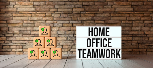 cubes with person-symbols stacked as a pyramid and lightbox with text HOME OFFICE TEAMWORK in front of a brick wall