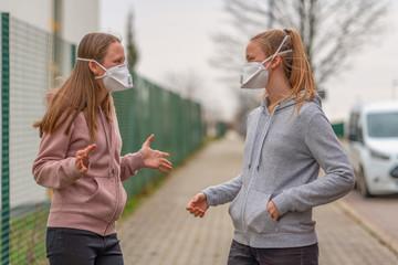 2 Jugendliche Mädchen Menschen mit Atemmaske auf der Straße in Deutschland wegen Coronavirus