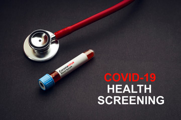 COVID-19 HEALTH SCREENING text with stethoscope and blood sample vacuum tube on black background. Covid or Coronavirus Concept