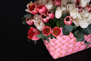 Foto op Canvas Lelie White and pink tulips in a pink wicker basket on a black background.
