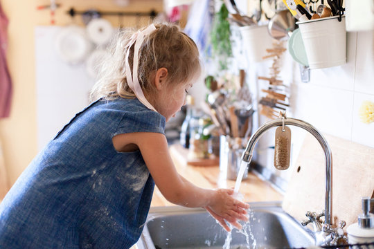 Kid washing hands at home under water tap. Cute child girl in flour after cooking in cozy home kitchen. Infection prevention. Avoid spreading viruses and germs.