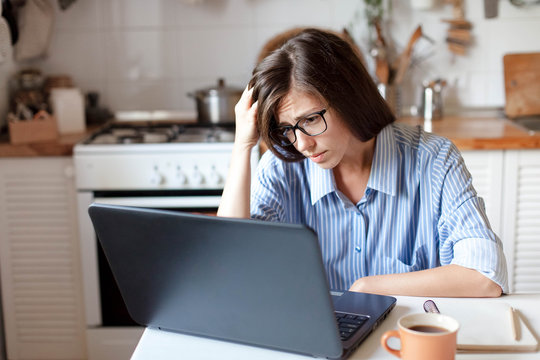 Upset woman working from home office. Worry freelancer using laptop and the Internet. Workplace in cozy kitchen. Concept of female business and career, housekeeping, stress. Lifestyle moment.