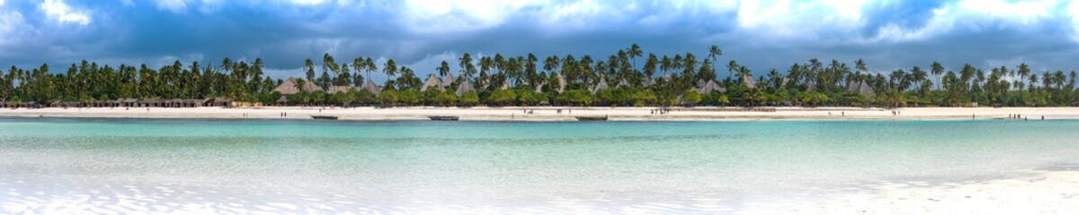 Foto auf Leinwand Sansibar panoramic view of the beach in zanzibar with palm trees and old fishing boats