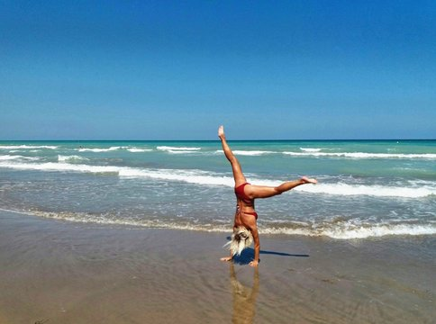 Rear View Of Woman In Bikini While Practicing Cartwheel At Beach Against Clear Sky