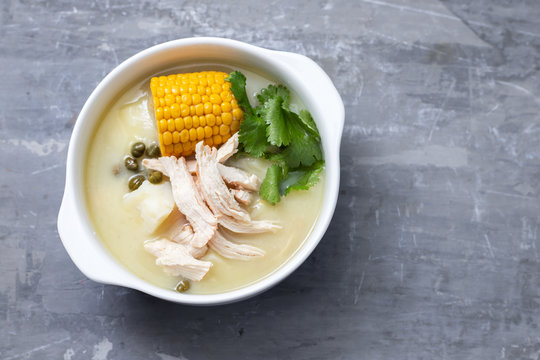 soup potato with corn and chicken in white bowl on ceramic background