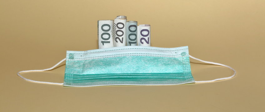 medical prtotective face / facial mask close up on pastel color background, behind rolls of banknotes 200, 100 and 20, concept of price / costs of coronavirus problem / protection