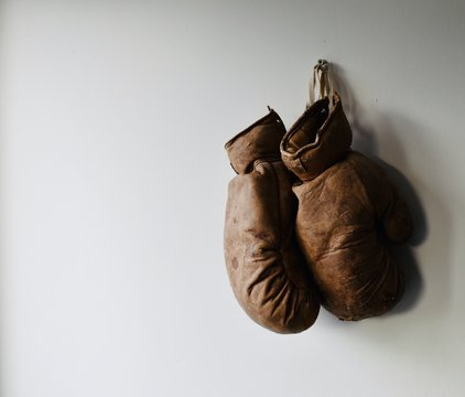 Pair of old and worn boxing gloves hang on the wall