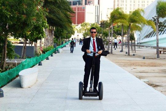 Businessman Riding Segway On Footpath