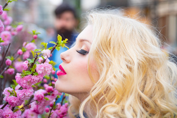 Beautiful woman with spring blooming flowers. Beautiful girl next to a bunch of flowers and smiling - outdoors.